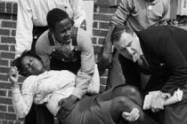 """FILE - In this March 7, 1965 file photo, S.W. Boynton is carried and another injured man tended to after they were injured when state police broke up a demonstration march in Selma, Ala. Boynton, wife of a real estate and insurance man, has been a leader in civil rights efforts. The day, which became known as """"Bloody Sunday,"""" is widely credited for galvanizing the nation's leaders and ultimately yielded passage of the Voting Rights Act of 1965. (AP Photo/File)"""